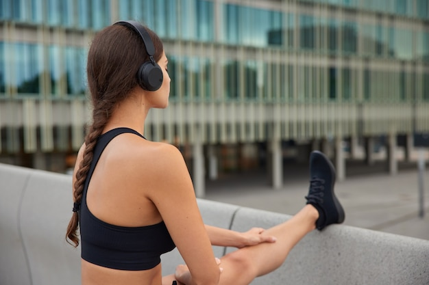 Woman in black cropped top sneakers stretches legs outdoors in modern environment warms up before workout poses on bridge near glass building enjoys favorite sound track