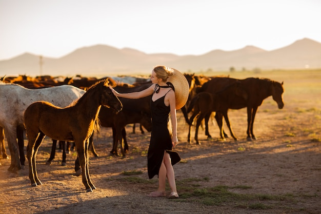 Woman in a black dress among wild horses
