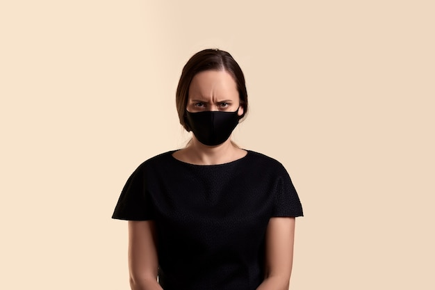 Woman in black dress and face mask frowns angry  over beige wall