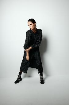 Woman in black dress fashion boots studio model