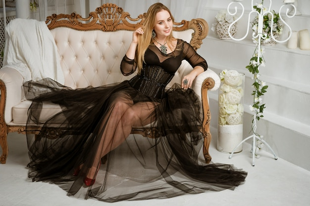 A woman in a black dress is sitting on a sofa in the interior