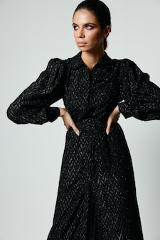 Woman in black dress looks aside fashion charm