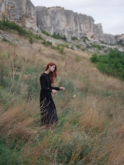 Woman in black dress outdoors in the mountains on a meadow in autumn