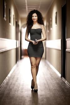 Woman in black dress walking along corridor