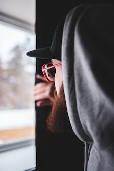 Woman in black hoodie wearing red framed eyeglasses