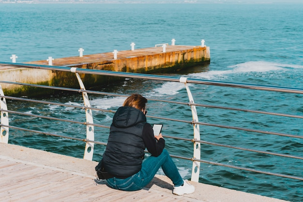 Woman in black jacket and jeans sits on the floor of pier and reading ebook. relaxation. self improvement. open air education. outdoor. blue wavy ocean. get fresh air. enjoy. embankment. seashore