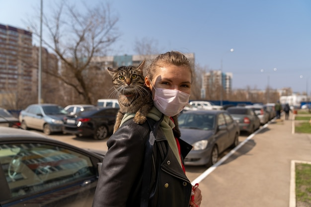 A woman in a black jacket put on a medical mask and walks on the street with a cat