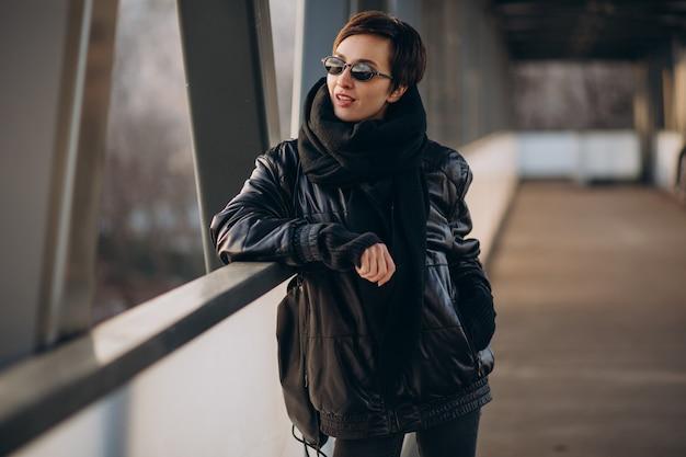 Donna in giacca nera che cammina attraverso il ponte
