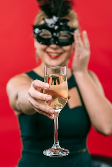 Woman in black mask holding champagne glass