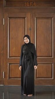 Woman in black muslim dress smiling looks beautiful in mosque