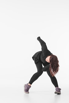 Woman in black outfit dancing against white backdrop