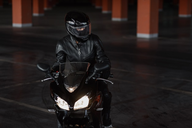 Woman in black protective uniform, gloves and full-face helmet riding on her motorcycle on underground parking.
