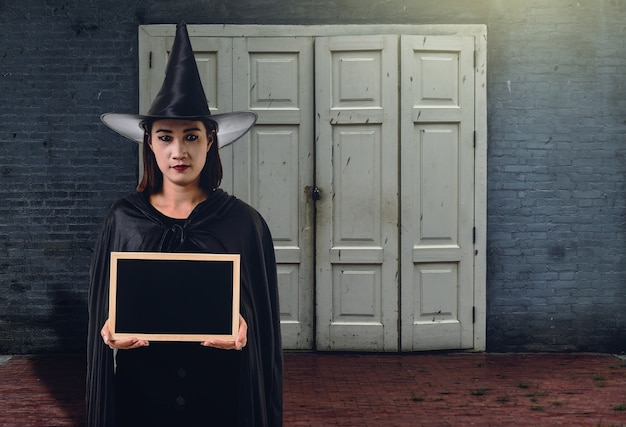 Woman in black scary witch halloween costume, holding chalk board with brick wall of ancie
