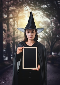Woman in black scary witch halloween costume, holding chalk board with moonlight in a dark fores