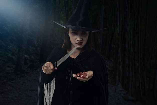 Woman in black scary witch halloween costume, holding a knife with moonlight in a dark forest