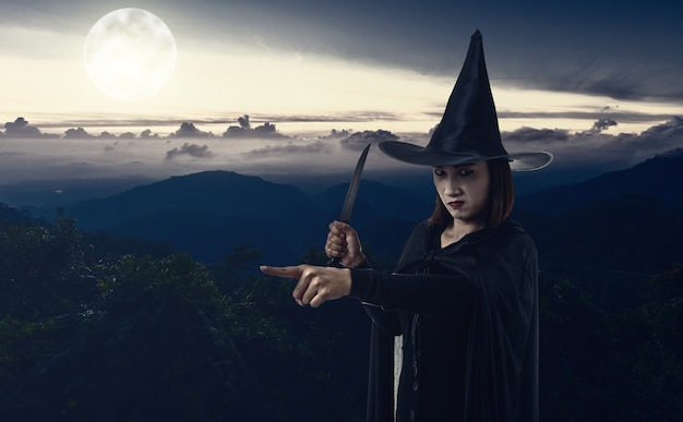 Woman in black scary witch halloween costume holding a knife with moonlight mountain and s