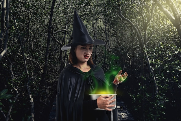 Woman in black scary witch halloween costume holding spooky witch's cauldron in a dark for