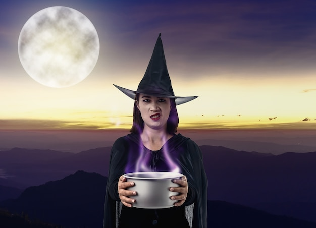 Woman in black scary witch halloween costume holding spooky witch's cauldron mountain, sea