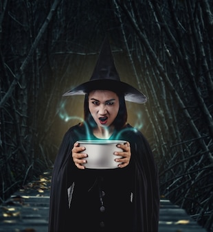 Woman in black scary witch halloween costume holding spooky witch's cauldron out in dark f
