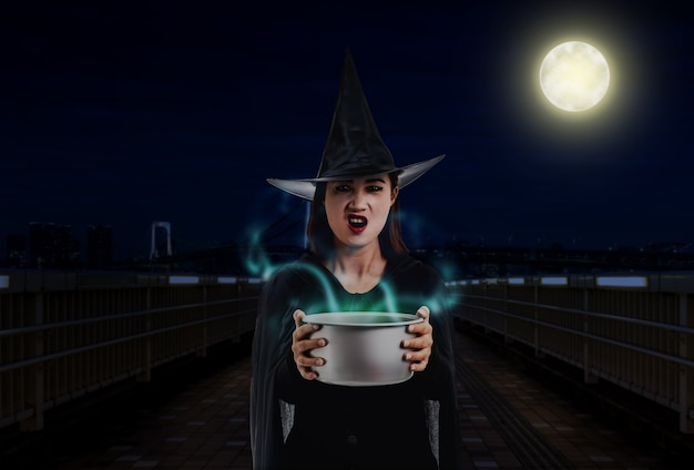 Woman in black scary witch halloween costume holding spooky witch's cauldron smoke coming out