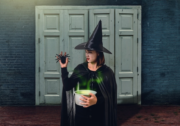 Woman in black scary witch halloween costume holding spooky witch's cauldron with cement w