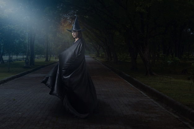 Woman in black scary witch halloween costume with moonlight in a dark forest