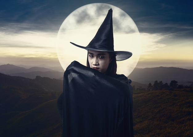 Woman in black scary witch halloween costume with moonlight. landscape mountain and sea of mist