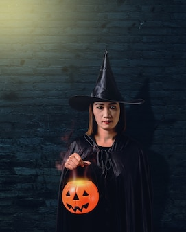 Woman in black scary witch halloween costume with old brick wall of the ancient castle of the witch