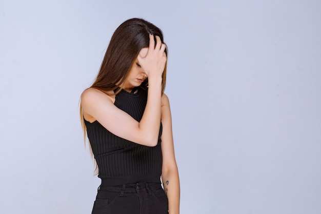 Woman in black shirt feeling sad or having headache.
