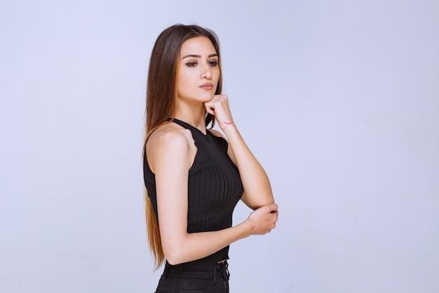 Donna in camicia nera che dà pose seducenti e accattivanti.