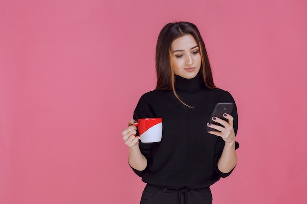 Woman in black shirt holding a coffee cup and talking to the phone.