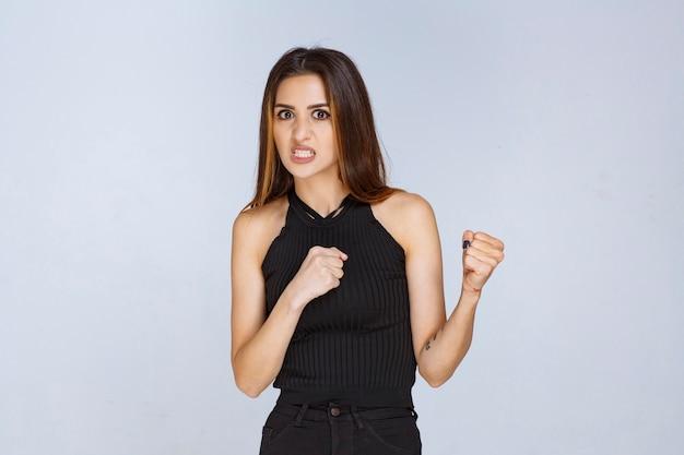 La donna in camicia nera sembra aggressiva e sconvolta.