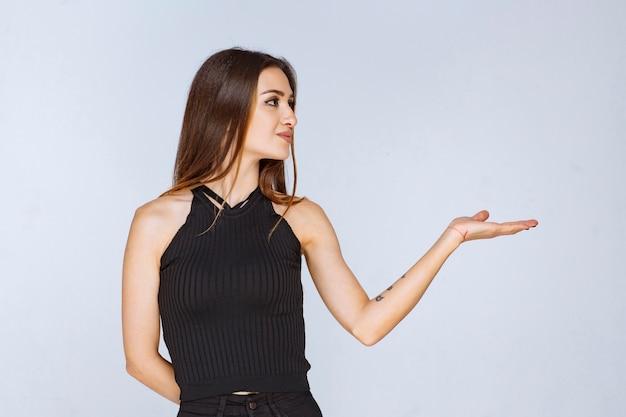 Donna in camicia nera che apre la mano e che tiene o che presenta qualcosa.
