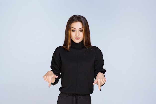 Woman in black shirt pointing at downside.