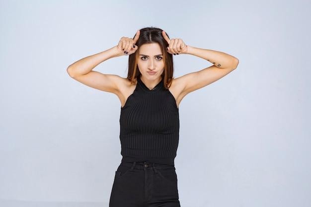 Donna in camicia nera che punta la testa e il pensiero.