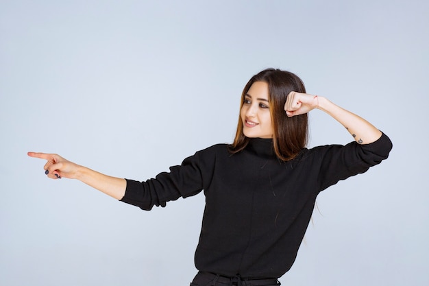 Donna in camicia nera che punta a sinistra e mostra le sue emozioni.