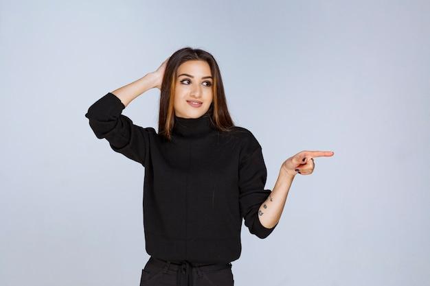 Donna in camicia nera che indica qualcosa a destra.