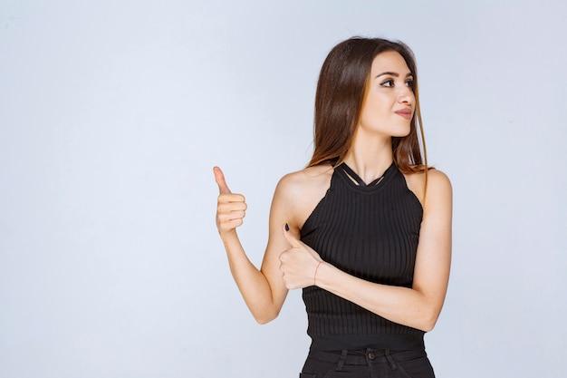 Woman in black shirt pointing something behind.