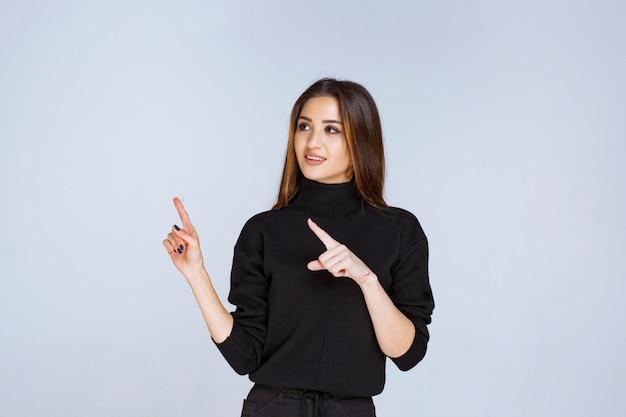 Donna in camicia nera che indica sopra.