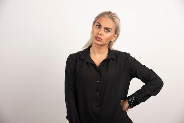 Donna in camicia nera in posa su sfondo bianco. foto di alta qualità