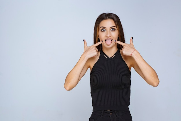 Woman in black shirt putting her tongue out.