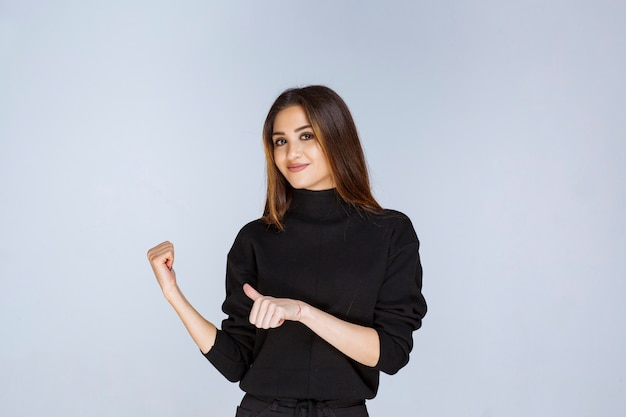 Woman in a black shirt showing enjoyment sign.