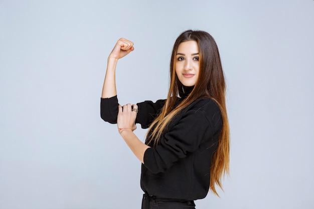 Donna in camicia nera che mostra i suoi pugni come simbolo del potere.