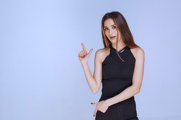 Woman in black shirt showing loser hand sign.