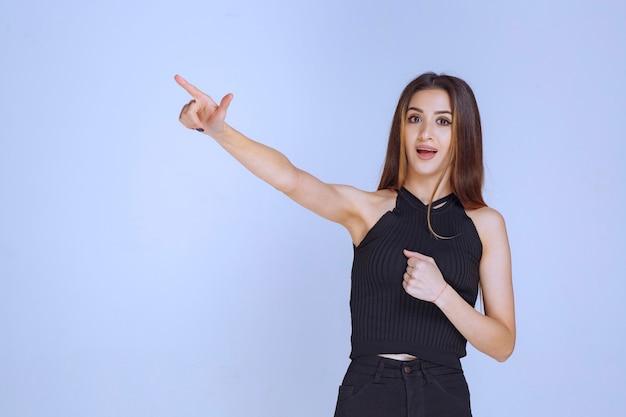 Donna in camicia nera che mostra il segno della mano del perdente.
