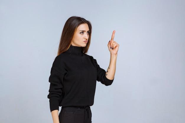 Donna in camicia nera che mostra il dito puntato e fa il prepotente con qualcuno.