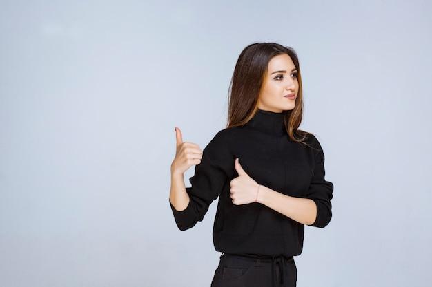 Donna in camicia nera che mostra il segno positivo della mano.