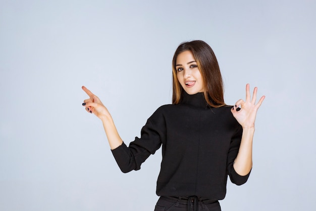 Woman in black shirt showing positive hand sign.