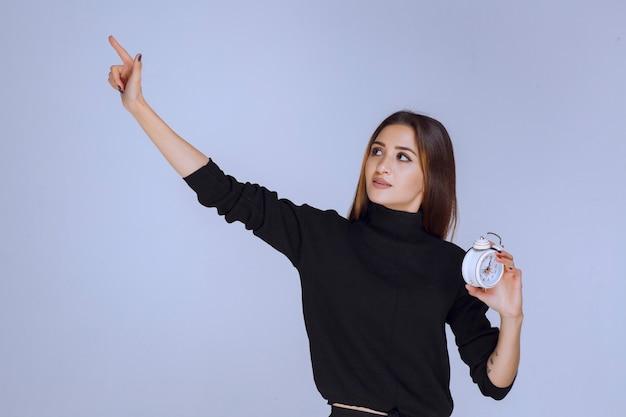 Donna in camicia nera che mostra qualcosa a sinistra.