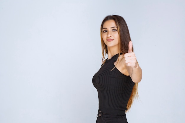 Woman in black shirt showing thumb up sign.